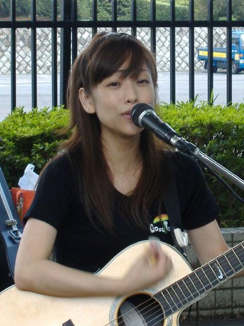 ギターを弾きながらマイクの前で歌を歌う椎名法子