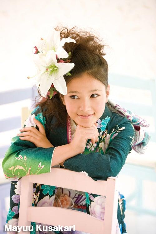 頭に飾った大きな花と色鮮やかな緑の服が美しい草刈麻有
