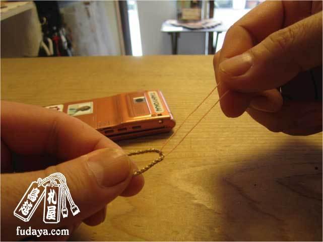 $-糸を根付の紐に通します