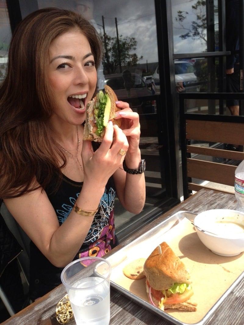 大きなサンドイッチを食べている武田久美子