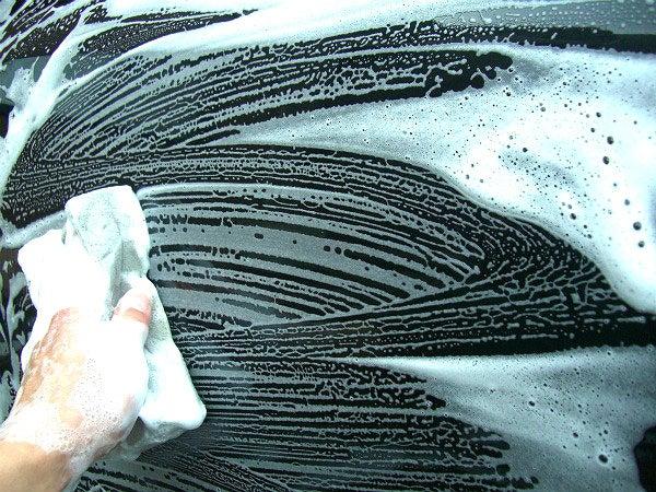 車のボディーに付着した水垢や油脂汚れをシャンプー洗車で落とす