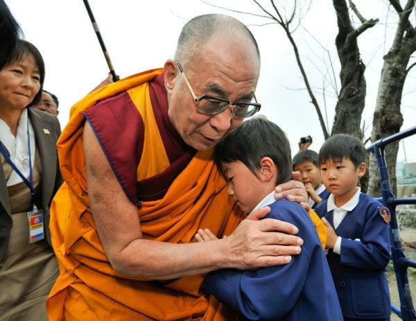 東日本大震災で幼児の肩を抱いて祈るダライラマ14世
