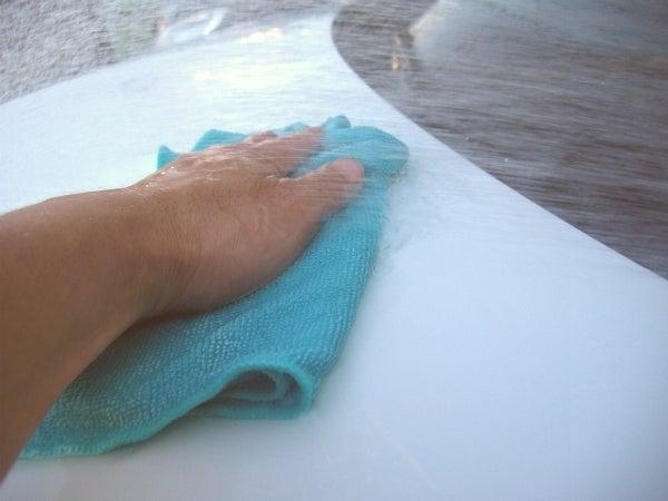 車のボディに刺さった鉄粉を水とクロスで洗い流す