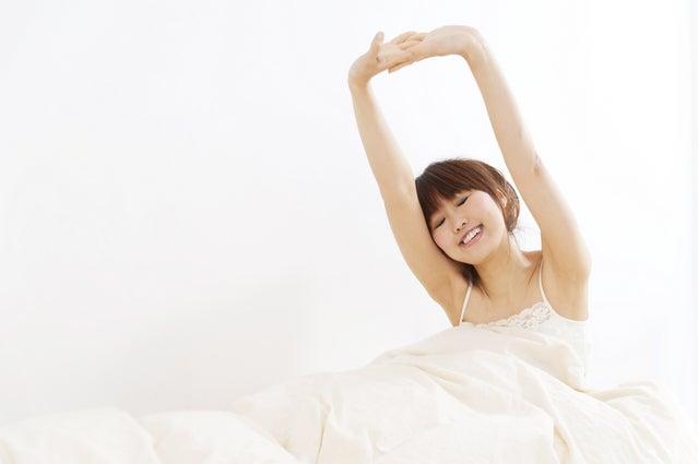 気持ち良く目覚めた女性の写真