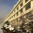 朝日に輝く校舎とグラ…