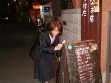 看板のメニューの写真に集中する社労士さん