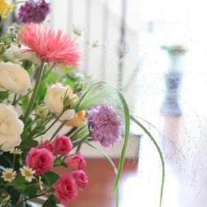 グリーンの枝物とガラスの花器の画像
