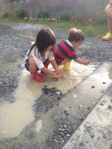 水たまりで遊ぶ姉弟