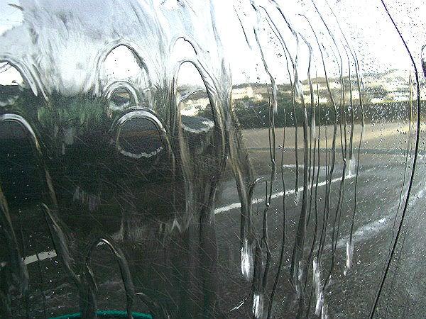 車のボディーガラス系コーティングを施工後水をかけて全体になじませる