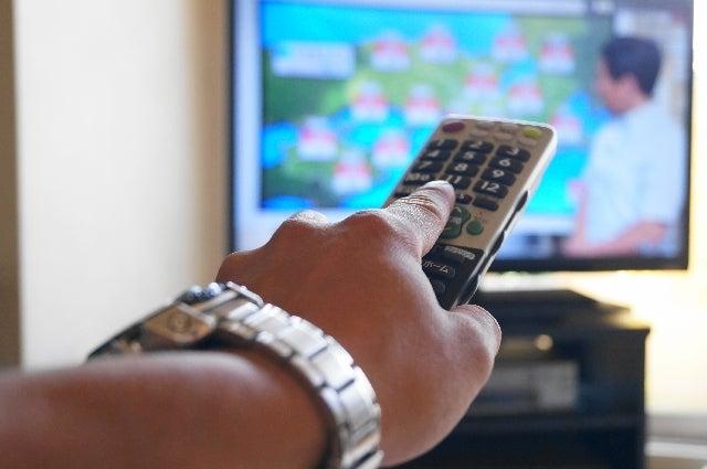 テレビとリモコンを持った手のアップ