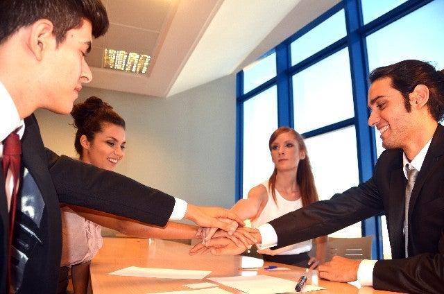 会議室で手を合わせている男女