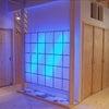 青い照明と墨を使った玄関の画像