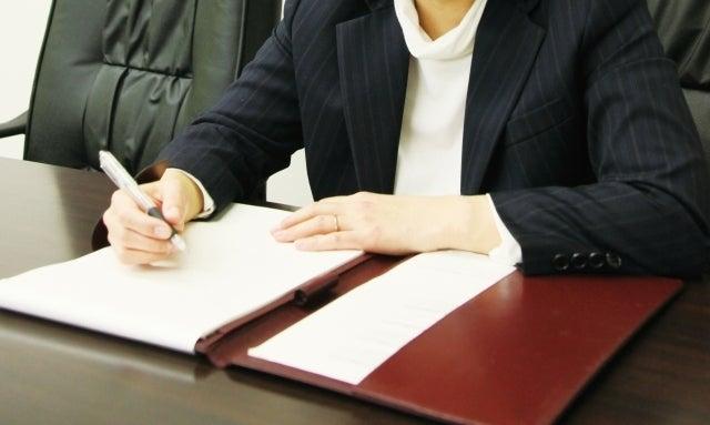 会社でノートのメモしている女性