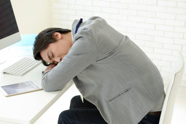 机に伏せて寝ている男性