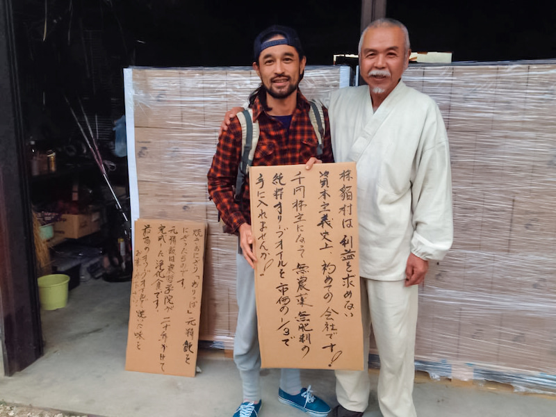 唖樵さんと三宅洋平、愛知・長久手の倉庫に積まれたオリーブオイルの前で