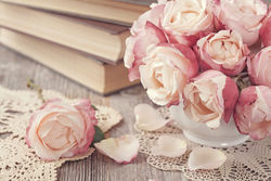 stock-photo-pink-roses-and-old-books-on-wooden-d