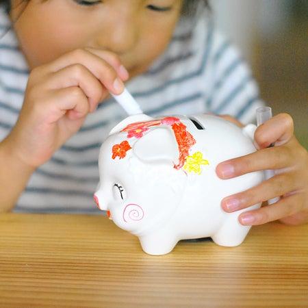 豚の貯金箱に色を塗っている女の子