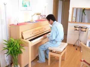 アップライトピアノに座り久々にピアノを弾く木村章司選手