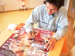 試合のポスターにマジックでサインをする木村章司選手