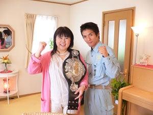 チャンピオンベルトを方に掛けてもらいガッツポーズを決める福田りえと木村章司選手