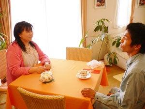 テーブルに向かい合って座り談笑する福田りえと木村章司選手