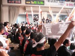 赤い幟が立ち並ぶ客席の一角を占めている黒いTシャツを着た木村章司選手の応援団の様子