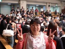 退場する木村章司選手を取り囲む黒いTシャツの応援団をバックに、ピースサインで記念撮影する福田りえ