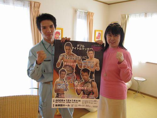 試合ポスターを挟んでチャンピオン木村章司選手とガッツポーズを決める福田りえ