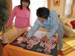 テーブルの上で試合ポスターにマジックでサインを書いている木村章司選手