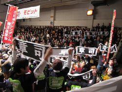 黒いTシャツで揃えた応援団が、手に手に「章司」書かれたタオルを振っている客席の様子