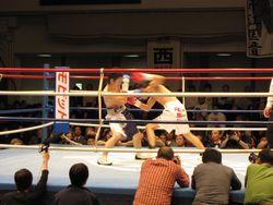 大ぶりのフックを放つ木村選手(右)と、それを避ける芹江選手(左)のリング上の様子