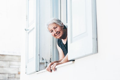 窓から顔を出す年配の女性画像