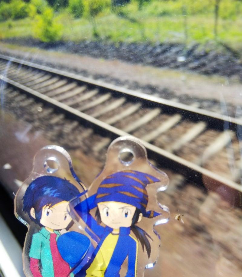 輝一と輝二のアクリルカードと線路の写真