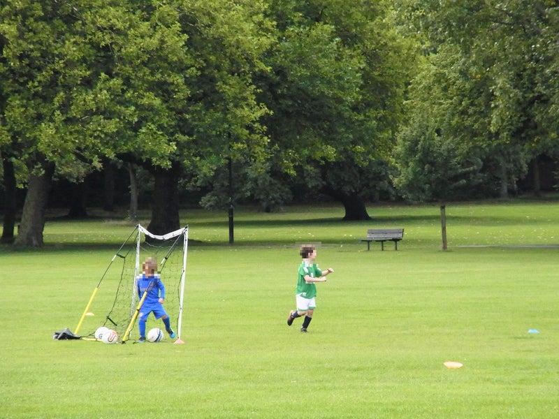 ロンドンの公園でサッカーをする少年たち