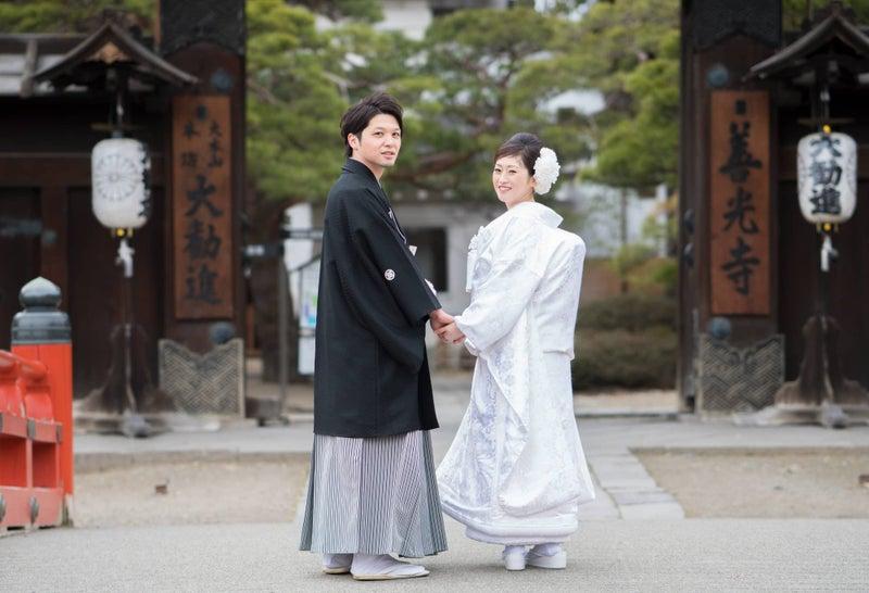 お寺の門の前で手をつなぐ新郎新婦
