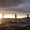 海の上のヨガ、夕日をバックに木のポーズの画像