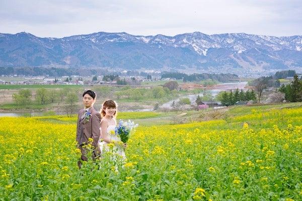 菜の花畑でウェディングフォトをする新郎新婦