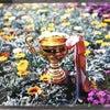 花と優勝カップで写真撮影の画像