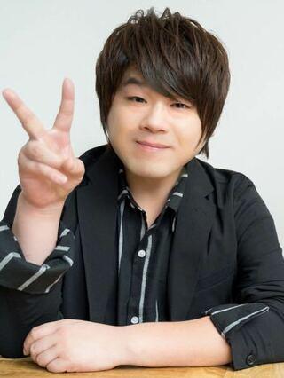 黒いジャケットを着ている声優の松岡禎丞
