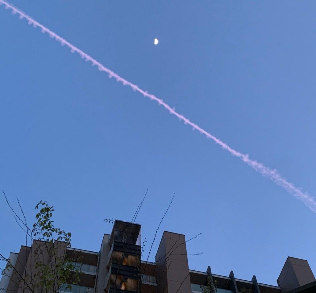 上弦の月とピンクの飛行機雲