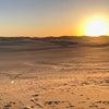 シワ砂漠での夕陽と満月の画像