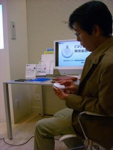 いとおしそうにC@T-oneを触る新田氏
